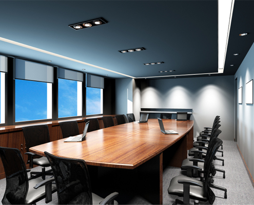 A conference room with a table and chairs and laptops