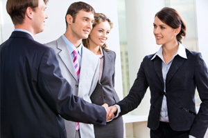 Women shaking hands with people after a meeting