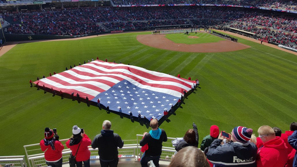 People holding the American Flag on the baseball field