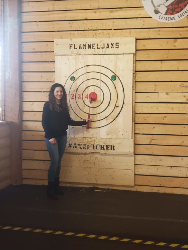 Woman standing next to a target with an axe in the target bullseye